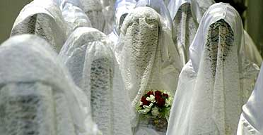 Muslim brides wait for the start of their mass wedding