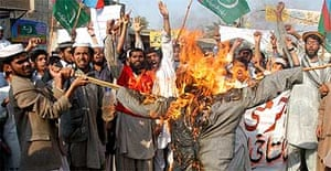 Pakistani religious students burn an effigy of Denmark's PM