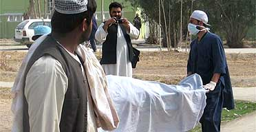 A medical attendant pushes the body of a police officer after he was killed in a suicide bombing in Kandahar, Afghanistan