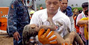 A rescue worker carries a child from the landslide in Leyte. Photograph: EPA
