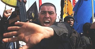 Iraqi Shia men brandish their weapons and chant slogans as they protest the bombing of the holy Shia shrine in Samarra
