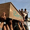 Family members and friends of an Iraqi police officer load his body onto a car in Baghdad
