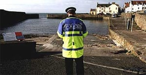 A policeman monitors Cellardyke harbour in Fife