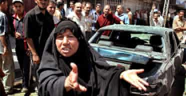 A woman gestures as soldiers secure the scene after two roadside bombs exploded in Baghdad. Photograph: Karim Kadim/AP