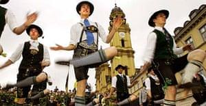 Men wearing traditional Bavarian outfits dance at Munich's Oktoberfest. Photograph: Joerg Koch/AFP/Getty