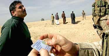 Marines check an Iraqi man's identity in Haditha