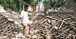 A man walks on the rubble of a house flattened by an earthquake in Grogol near Yogyakarta, Indonesia