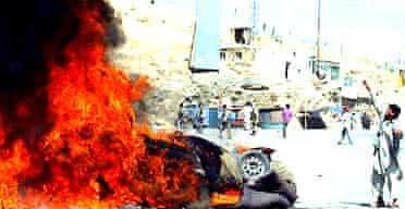An Afghan protestor throws a stone at police near a burning police vehicle in Kabul. Photograph: Zabi Tamanna/AP