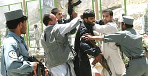 Afghan police officers detain a protester in Kabul