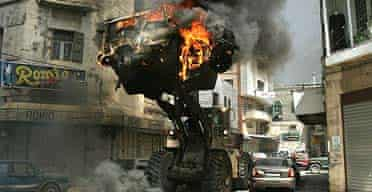 A bulldozer moves an Israeli army jeep set alight during clashes in Nablus