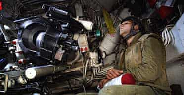 An Israeli soldier sleeps in the cockpit of a mobile artillery unit