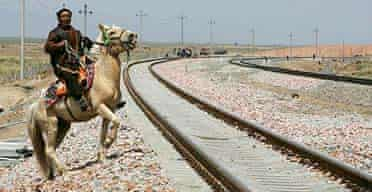 A Tibetan man rides his horse along the tracks of the Qinghai-Tibet railway