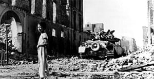 A British tank looms behind an Egyptian boy amid the rubble of Port Said during the Suez crisis. Photograph: Hulton-Deutsch Collection/Corbis