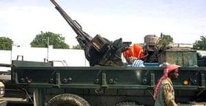 An Islamist fighter walks past an anti-aircraft machine gun seized from Abdi Awale Qaybdiid