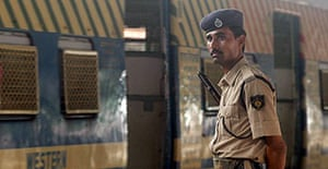 An Indian policeman stands guard at a railway station in Mumbai