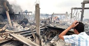 A Lebanese youth checks a destroyed factory near the eastern Lebanese village of Jezzine, east of Sidon, following Israeli air raids