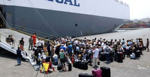Swedish nationals wait to board a Malaysian vessel at Beirut port as part of an evacuation at the port in Beirut.