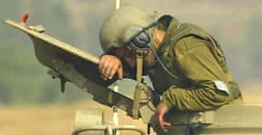 An Israeli gunner rests on top of a artillery piece near Kiryat Shmona, northern Israel, next to the Lebanese border