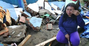 An Indonesian woman weeps as she sits amid the rubble of her house in Pangandaran, Java.