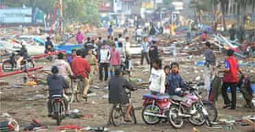 Residents walk through a tsunami-devastated area in Pangandaran, West Java, Indonesia