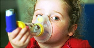 A young asthma sufferer uses her inhaler