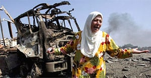 A Lebanese woman cries in front of a destroyed truck in southern Beirut