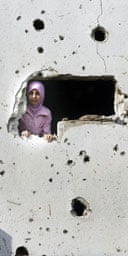 A girl peers out from her family's damaged home near Sidon in southern Lebanon.