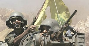 Israeli soldiers holding up the yellow Hizbullah flag as they roll back across the border from southern Lebanon into northern Israel