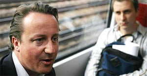 David Cameron speaks to commuters on a train to Waterloo, London