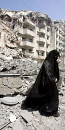 A Lebanese woman makes her way through rubble in southern Beirut.