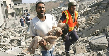 A man screams for help as he carries the body of a dead girl after Israeli air strikes on the southern Lebanese village of Qana