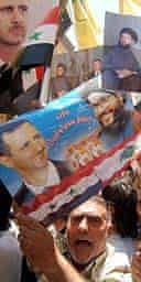 Demonstrators in Damascus carry pictures of Hizbullah leader, Hassan Nasrallah, and Syrian president, Bashar al-Assad