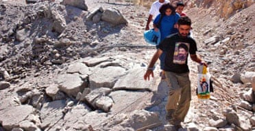 A Lebanese man wearing a T-shirt with a picture of Hezbollah leader Sheik Hassan Nasrallah, walks past a bomb crater in the eastern Bekaa valley.