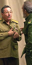 Raul Castro (left) speaks with Fidel at the Convention Palace, Havana