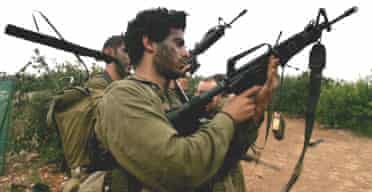 Israeli soldiers unload their weapons along the Israel-Lebanon border after a mission into Lebanon.