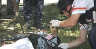 An Israeli rescue worker tends to the body of a man killed in a Hizbullah rocket attack on the Sahar kibbutz.