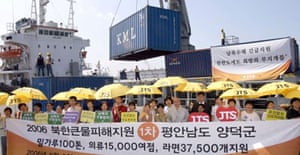 Members of JTS Korea, a Seoul-based relief agency, watch as a consignment of emergency aid is loaded for shipment to North Korea.