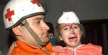 A young Lebanese girl is carried by a Red Cross worker after being injured in an air strike