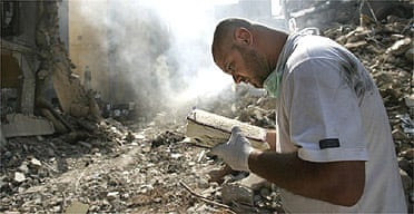 Lebanese man retrieves a Qur'an from under the debris of a destroyed building