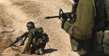 Israeli troops on a dirt road on the Lebanon side of the border after crossing from northern Israel
