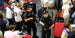 Armed police walk through crowds of people at Gatwick airport. Photograph: Carl De Souza/AFP/Getty