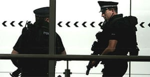 Armed police officers patrol Glasgow Airport terminal