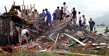 Villagers search the rubble of a collapsed house in Cangnan county after Typhoon Saomai battered areas of eastern China. Photograph: AP
