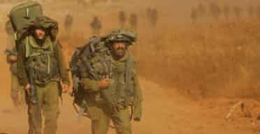 Israeli soldiers cross the border from southern Lebanon back into Israel