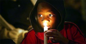 A child attends a vigil for Aids victims in Ngwenya