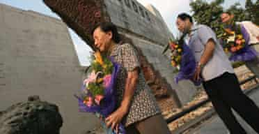 Nanjing survivor Xia Shuqin (l) lays flowers in memory of the victims of the massacre