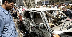 Iraqis check a destroyed taxi after a roadside bomb was set off in Baghdad's Shurja market