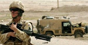 A British soldier stands guard at the site of a roadside bomb attack in Basra, Iraq