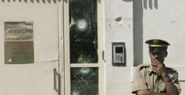 A Syrian policeman stands next to a door marked with bullet holes at the US Embassy in Damascus, after an attack by four gunmen.