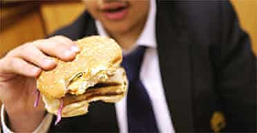 A schoolboy eats a burger for lunch